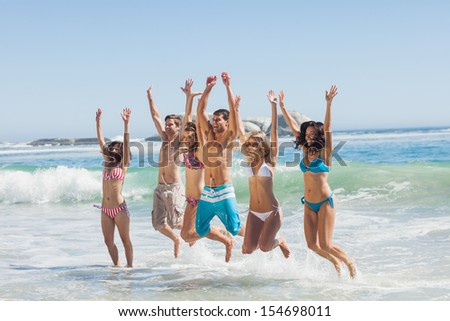 Happy friends jumping and having fun on beach on holidays - stock photo