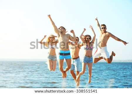 Happy friends jumping at the beach, outdoors - stock photo