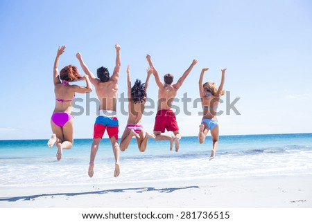 Happy friends jumping together at the beach