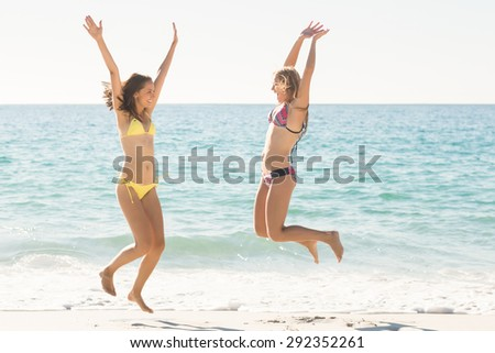 Happy friends jumping together at the beach - stock photo