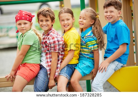 Happy friends looking at camera with smiles on playground - stock photo