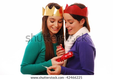 Happy friends looking at joke from christmas cracker on white background - stock photo