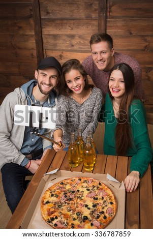 Happy friends making top view selfies in pizzeria. Beautiful people trying to save best moments in best company of friends. - stock photo