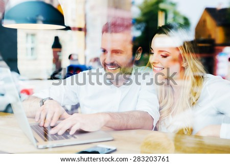 Happy friends meeting at cafe with laptop. - stock photo