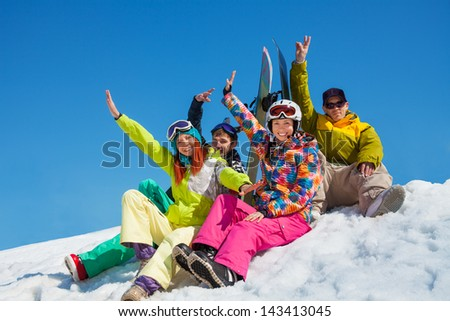 Happy friends men and women sit in snow with snowboards lifting and waving hands - stock photo