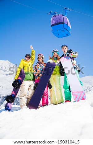 Happy friends men and women stand in snow holding snowboards lifting and waving hands and cable car ski lift - stock photo