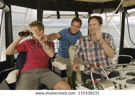 Happy friends on yacht looking at something - stock photo