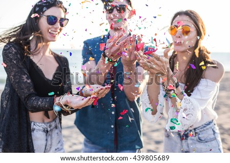 Happy friends partying on the beach with confetti  - stock photo