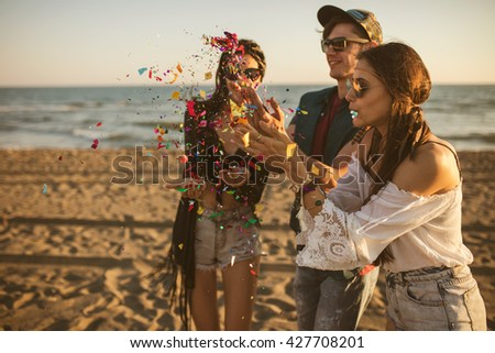 Happy friends partying on the beach with drinks and confetti.  - stock photo