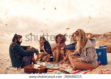 Happy friends partying on the beach with drinks and confetti. Happy young people having fun at beach party, celebrating with confetti. - stock photo
