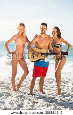Happy friends posing and playing guitar on the beach on a sunny day