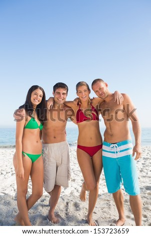 Happy friends posing together on the beach