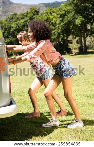 Happy friends pushing their mini van on a summers day - stock photo