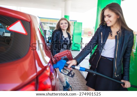 Happy friends refuel car in gas station. Holiday trip of friends - stock photo