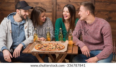 Happy friends resting in pizzeria and communicating. Modern young beautiful people eating pizza and drinking delicious cocktails. - stock photo