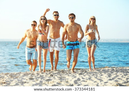 Happy friends running at the beach, outdoors - stock photo