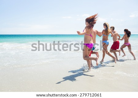 Happy friends running in the water together at the beach - stock photo