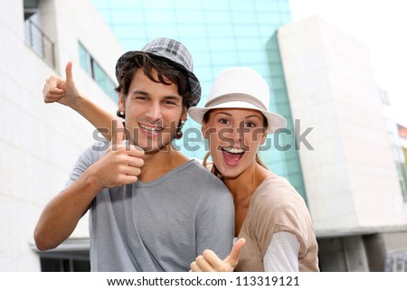 Happy friends showing thumbs up - stock photo