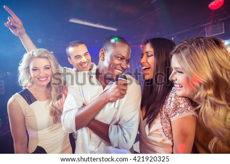Happy friends singing at the karaoke in night club - stock photo