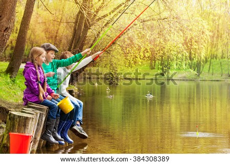 Happy friends sitting and fishing together near the pond with colorful fishrods in beautiful forest landscape