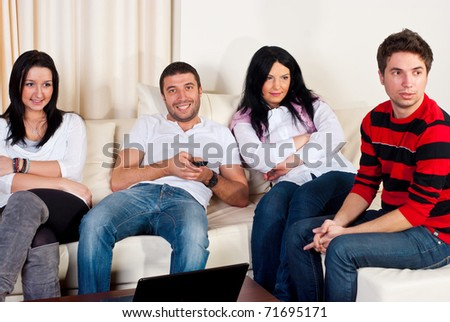 Happy friends sitting comfortable on couch and watching tv - stock photo