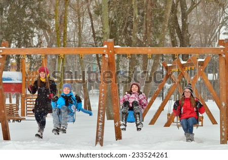 Happy friends sitting on swing in park in winter time - stock photo