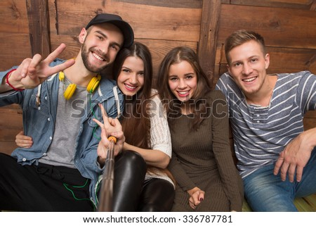 Happy friends sitting on the floor, smiling for the camera. Handsome man in black cap showing yo sign isolated on wooden background. - stock photo