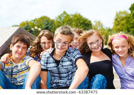 Happy friends sitting together outside - stock photo