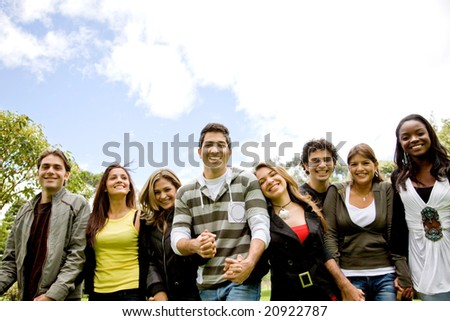 happy friends smiling outdoors in a park - diversity - stock photo