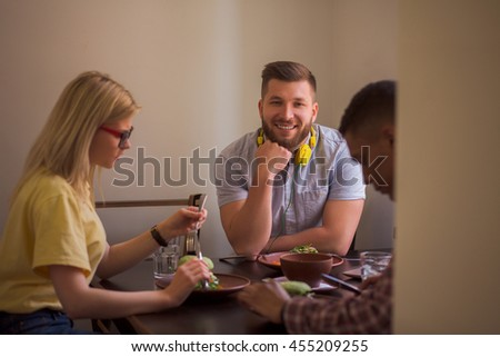 Happy friends spending their free time in vegan restaurant or cafe. Smiling man looking at camera while his friends eating healthy vegan dishes. - stock photo