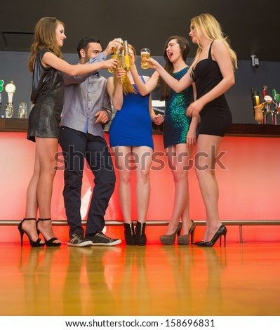 Happy friends standing at a bar and clinking glasses - stock photo
