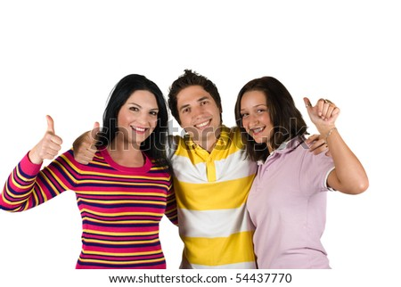 Happy friends standing in a hug and giving thumbs up - stock photo