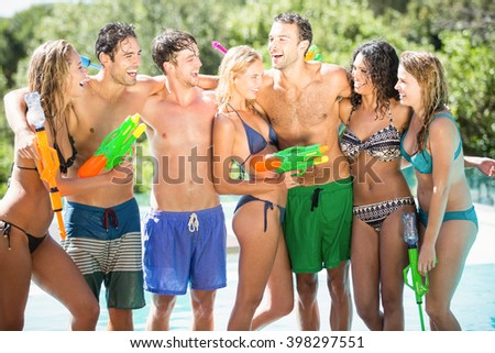 Happy friends standing together near swimming pool with water guns - stock photo