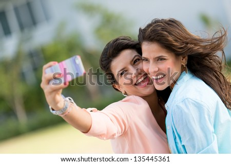 Happy friends taking a self portrait with a cell phone - stock photo