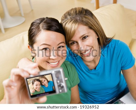 Happy friends taking self-portrait with digital camera - stock photo