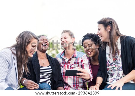 Happy friends taking selfie and laughing