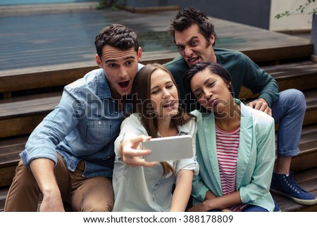 Happy friends taking selfie outside the bar - stock photo