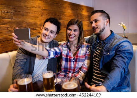 Happy friends taking selfie through mobile phone at restaurant - stock photo
