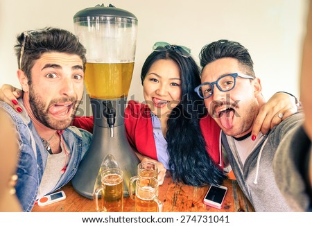 Happy friends taking selfie with funny tongue out near beer tower dispenser - Concept of friendship and fun with new trends and technology -  Alternative everyday party life in vintage brewery bar - stock photo