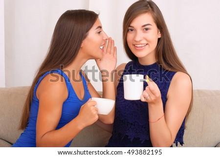 happy friends talking and drinking coffee and tea sitting on a couch at home and gossiping