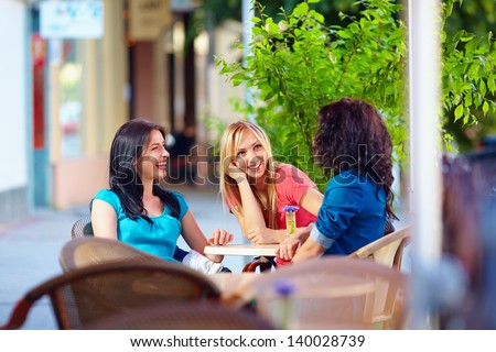 happy friends talking in summer cafe, urban outdoors - stock photo