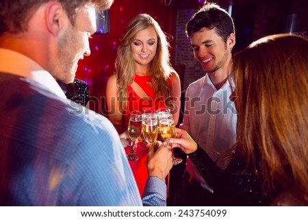 Happy friends toasting with champagne at the nightclub - stock photo