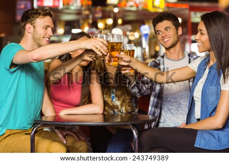 Happy friends toasting with drink and beer in a pub - stock photo