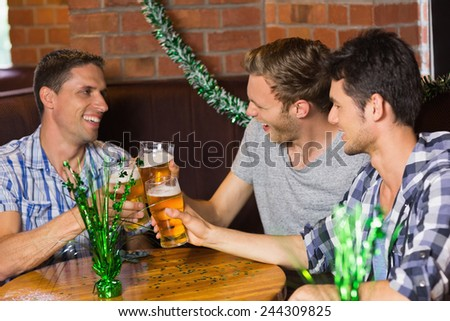 Happy friends toasting with pints of beer on patricks day in a bar - stock photo