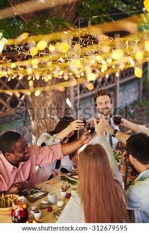 Happy friends toasting with red wine at Thanksgiving party - stock photo