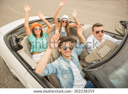 Happy friends traveling on the cabriolet with hands up. - stock photo