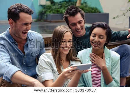 Happy friends using smartphone outside the bar - stock photo