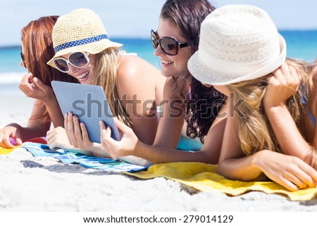 Happy friends wearing sun glasses and using tablet at the beach - stock photo