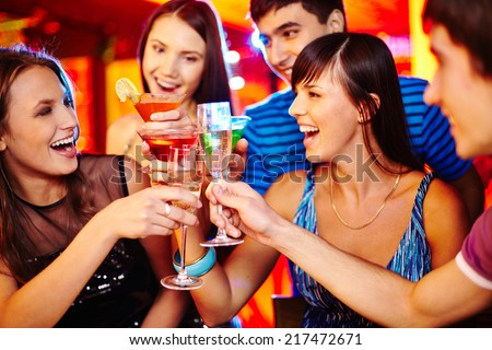 Happy friends with flutes of sparkling champagne enjoying the party