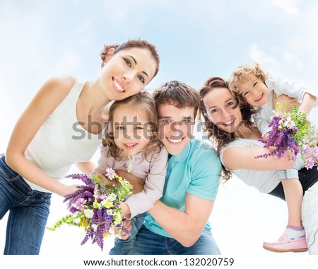 Happy friends with kids having fun outdoors in summer against blue sky background. Family vacations concept. Low angle view - fisheye lens. - stock photo